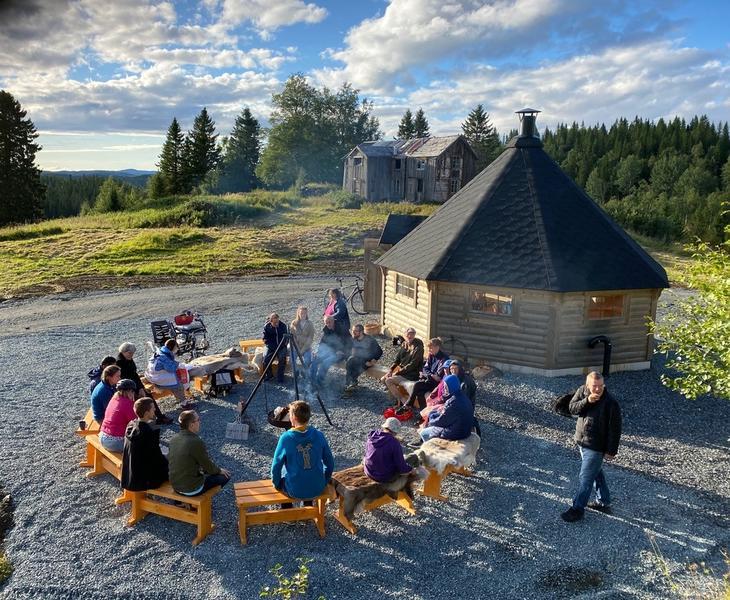 Alle på Jøssåsen er samlet og sitter på benker rundt bålpanna som står ved siden av grillhytta. I bakgrunnen skog og en forfallen gård.